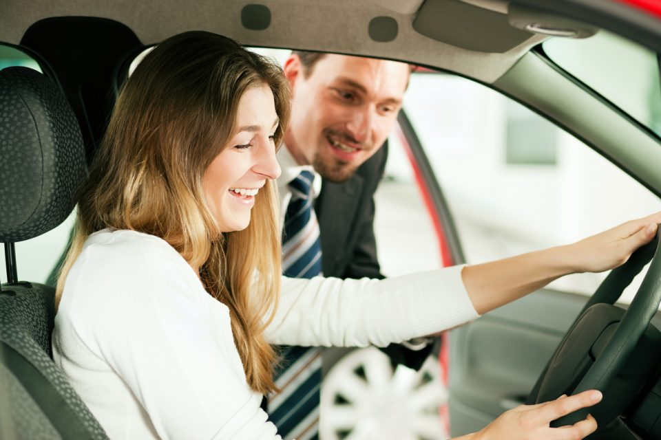Close-up of woman in car with car salesman