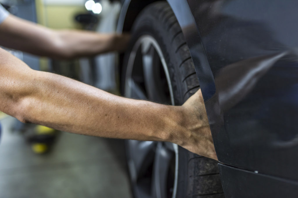 Hands of mechanic changing a wheel of a modern car